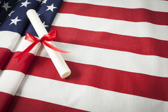 Ribbon Wrapped Diploma Resting on American Flag with Copy Space Stock Image
