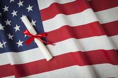 Ribbon Wrapped Diploma Resting on American Flag with Copy Space Stock Photos