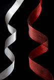 Ribbons. Red and silver ribbon on black background Stock Photography