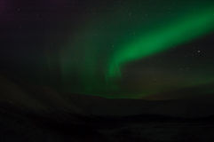 Ribbons of Aurora polaris. Above the tops of mountains stock images