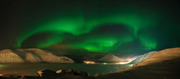 Ribbons of Aurora polaris above mountains. Panorama of Aurora polaris above mountains Stock Photo