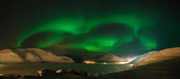 Ribbons of Aurora polaris above mountains. Panorama of Aurora polaris above mountains stock photo