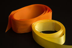 Ribbons on black background. Closeup of yellow and orange ribbons on black background Stock Image