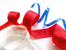 Ribbons - blue, red and white. Blue, red and white spiral ribbons on white background stock image