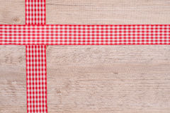 Ribbons of cloth red and white checkered. On a wooden board Royalty Free Stock Images