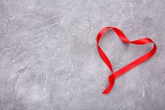 Ribbons shaped as hearts on grey concrete, valentines day concept stock photography