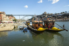 Ribeira, traditional boats at Douro river in Old Town, Luiz iron bridge in background. Stock Photo