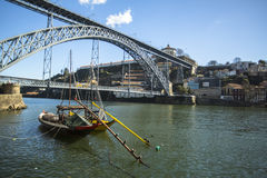 Ribeira, traditional boats at Douro river in Old Town, Luiz iron bridge in background. Royalty Free Stock Photos