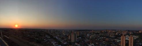 RIBEIRAO PRETO, SAO PAULO, BRASILIEN - Sonnenuntergang an der Allee und an den Gebäuden in der Stadt - Panoramablick Stockbild