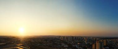 RIBEIRAO PRETO, SAO PAULO, BRASILIEN - Sonnenuntergang an der Allee und an den Gebäuden in der Stadt - Panoramablick Lizenzfreies Stockbild