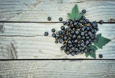 Ribes nero fresco su fondo di legno rustico Immagine Stock