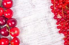 Ribes rosso e ciliege maturi freschi su fondo di legno rustico Immagini Stock