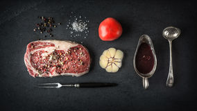 ribeye牛排大理石、蕃茄和大蒜片断在蓝色片岩 免版税库存图片