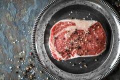 ribeye牛排大理石和干胡椒片断在锡板材  库存照片