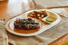 Ribeye牛排用迷迭香小树枝装饰了用在一块白色板材的油煎的土豆在木背景的一块灰色餐巾 免版税库存图片