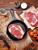 生铁平底锅用在木背景的未加工的ribeye牛排 库存照片