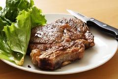 Ribeye steak. On a plate Royalty Free Stock Photos