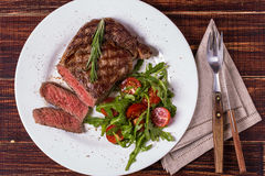 Ribeye steak with arugula and tomatoes. Ribeye steak with arugula and tomatoes on  dark wooden background Stock Images