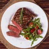 Ribeye steak with arugula and tomatoes. Royalty Free Stock Photo