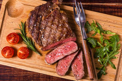Ribeye steak with arugula and tomatoes. Royalty Free Stock Images