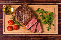 Ribeye steak with arugula and tomatoes. Royalty Free Stock Photos