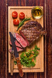 Ribeye steak with arugula and tomatoes. Royalty Free Stock Image