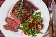 Ribeye steak with arugula and tomatoes. Ribeye steak with arugula and tomatoes on  dark wooden background Stock Photo