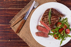 Ribeye steak with arugula and tomatoes. Stock Photos