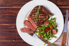 Ribeye steak with arugula and tomatoes. Royalty Free Stock Photo