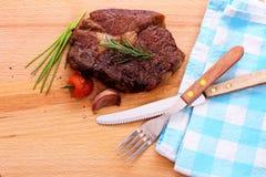 Ribeye steak with cherry tomatoes, garlic, herbs Stock Photo
