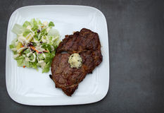Ribeye Steak with Cilantro Butter and a side salad keto meal. Fat filled Ribeye Steak with Cilantro Butter and a side salad topped with Ranch dressing. Perfect Stock Photography