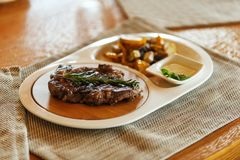 Ribeye steak decorated with a sprig of rosemary with fried potatoes in a white plate on a gray napkin on wooden background royalty free stock images