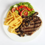 Ribeye steak dinner from above. A grilled ribeye steak served with mushrooms, chips (french fries) and a garden salad of lettuce, cucumber, baby carrot and royalty free stock photo