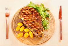 Ribeye steak with fresh greenery Stock Images