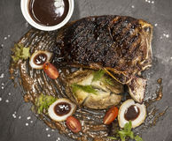 Ribeye steak from marble beef meat with vegetables and barbecue sauce. Served on a plate of black stone. Royalty Free Stock Images
