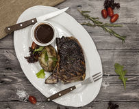Ribeye steak from marble beef meat with vegetables and barbecue sauce. Served on a plate of black stone with fork and knife . Stock Photo