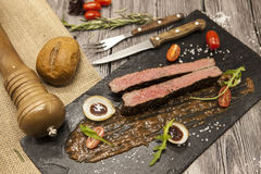 Ribeye steak from marble beef meat with vegetables and barbecue sauce. Served on a plate of black stone with fork and knife . Stock Photos
