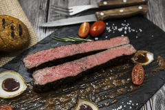 Ribeye steak from marble beef meat with vegetables and barbecue sauce. Served on a plate of black stone with fork and knife . Stock Photography
