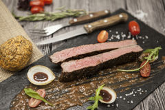 Ribeye steak from marble beef meat with vegetables and barbecue sauce. Served on a plate of black stone with fork and knife . Royalty Free Stock Photo