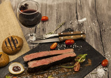 Ribeye steak from marble beef meat with vegetables and barbecue sauce. Served on a plate of black stone with fork and knife and wi Stock Photography
