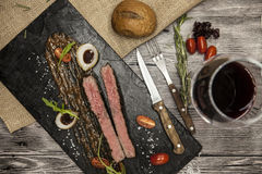 Ribeye steak from marble beef meat with vegetables and barbecue sauce. Served on a plate of black stone with fork and knife and wi Stock Photo