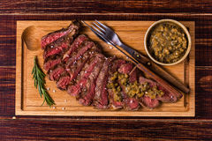 Ribeye steak and mustard sauce with pickles. Royalty Free Stock Image