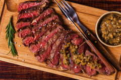 Ribeye steak and mustard sauce with pickles. Ribeye steak and mustard sauce with pickles on dark wooden background Stock Image
