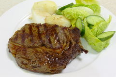 Ribeye steak side view. A meal of grilled or broiled ribeye steak served with boiled potato and a green salad stock image