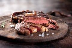 Ribeye-Steakscheiben mit Salz und Rosmarin Stockfoto