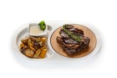 Ribeye stek dekorował z sprig rozmaryny z smażyć grulami w białym talerzu na odosobnionym białym tle obraz royalty free