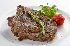 Ribeyelapje vlees met rozemarijn Op een witte plaat stock afbeeldingen