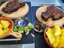 Riblapjes vlees op de houten plaat met smakelijke aardappels stock foto