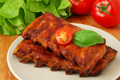 Ribs. Grilled ribs with tomatoes and lettuce royalty free stock photos