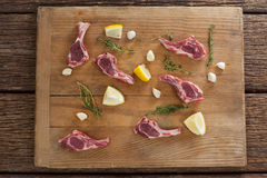 Ribs chops, lemon and garlic on wooden board Stock Photography